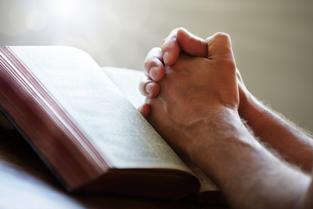 Hands folded in prayer on a Holy Bible